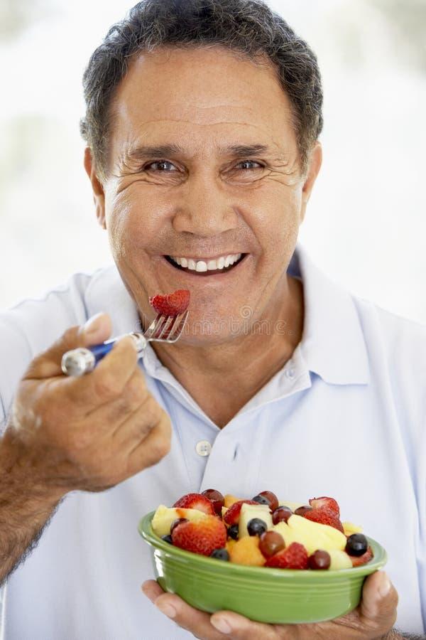 Senior Man Eating Fresh Fruit Salad royalty free stock image