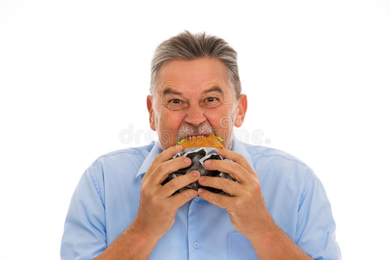 Senior man eating hamburger royalty free stock photo