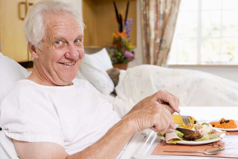 Senior Man Eating Hospital Food In Bed stock photo