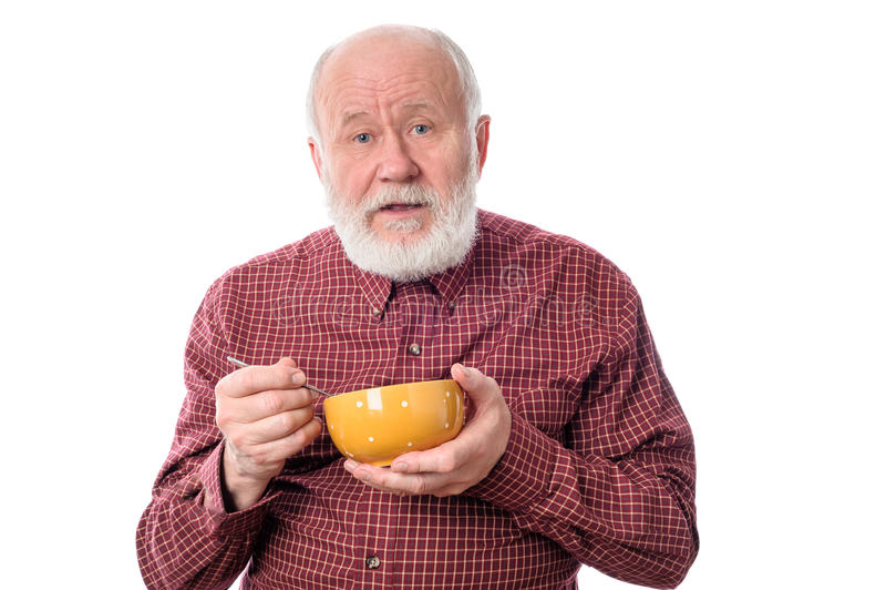 Senior man eating from oragne bowl , isolated on white stock photos
