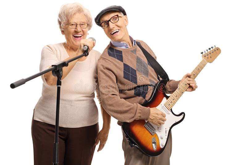 Senior man with an electric guitar and senior woman holding a microphone. Senior men with an electric guitar and senior women holding a microphone isolated on royalty free stock images