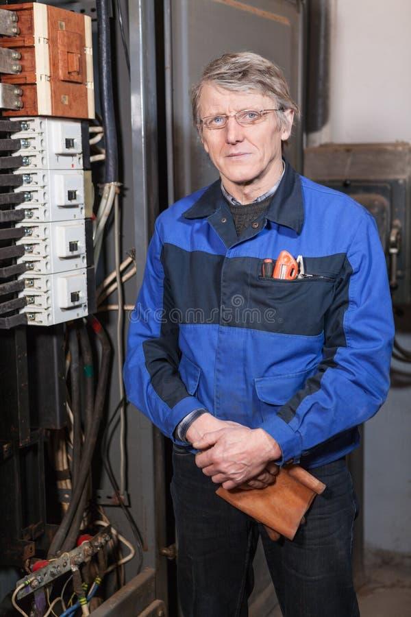 Senior man electrician in blue uniform standing near high voltage box stock photo