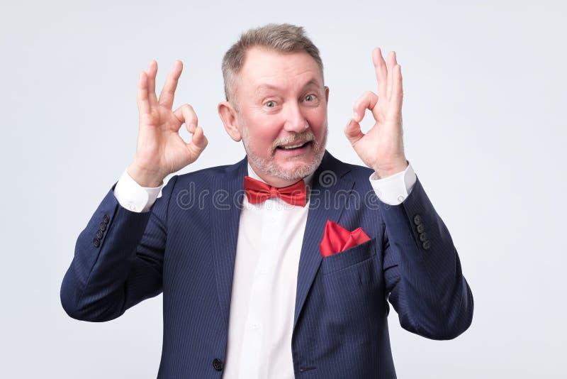 Senior man in elegant blue suit showing OK sign royalty free stock photography