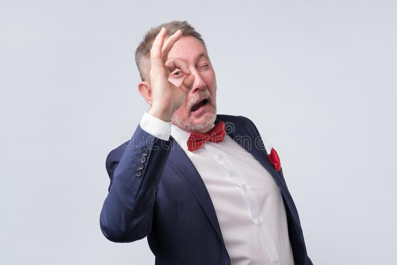 Senior man in elegant blue suit showing OK sign royalty free stock photos