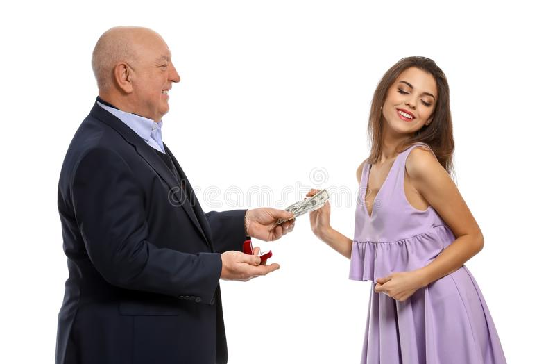 Senior man with engagement ring and money proposing to young woman on white background. Marriage of convenience. Senior men with engagement ring and money royalty free stock images