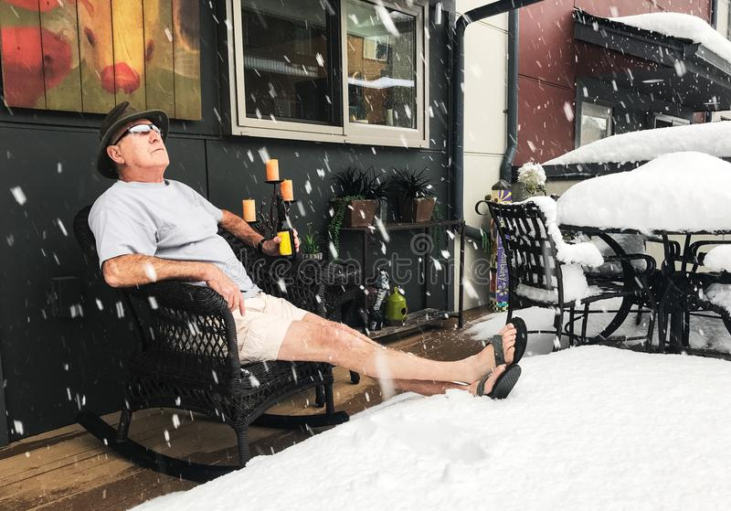 Man Drinks Beer in Winter Snow During Northwest Summer st. Senior man enjoys beer on shorts, hat and flip-flops in the midst of snow storm in the Pacific royalty free stock photos