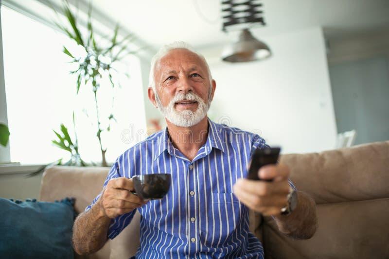 Senior man enjoys watching tv at home. Senior man watching tv and drink coffee royalty free stock photo