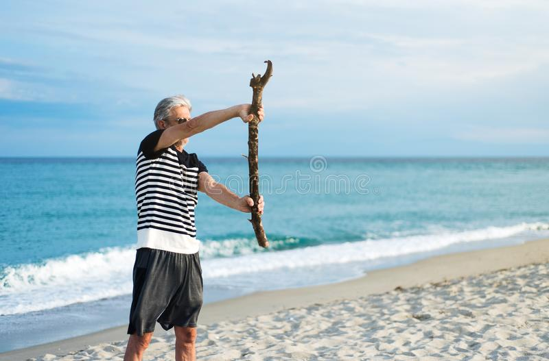 Senior man exercising on the beach. With a wooden log workout exercise stretching male seaside gray hair summer healthy positive active slim holiday old elderly stock images