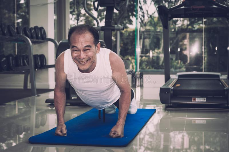 Senior man exercising by doing push ups in the fitness center,. Sport and health concept royalty free stock images
