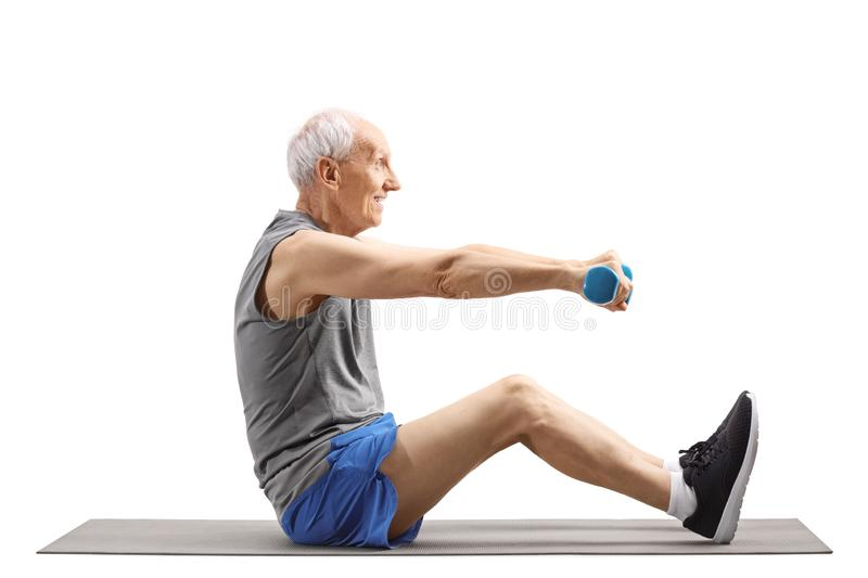 Senior man exercising with dumbbells and sitting on an exercise mat royalty free stock photography