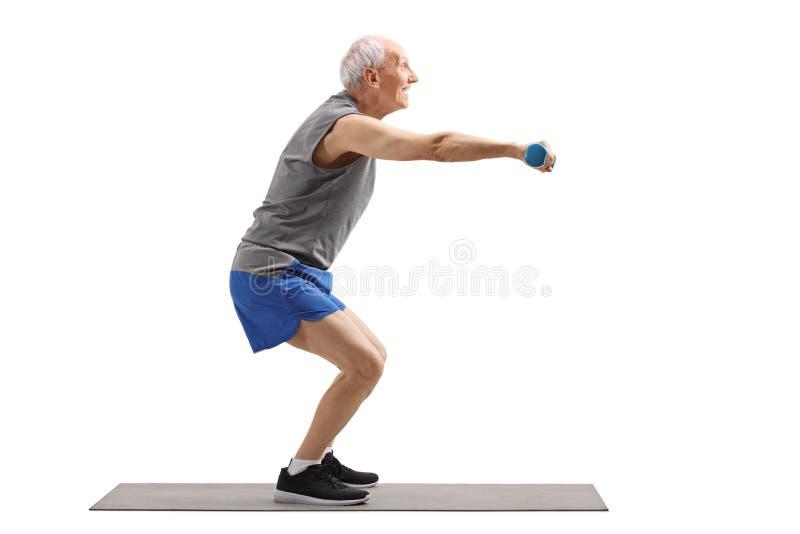 Senior man exercising squats and holding dumbbells. Full length profile shot of a senior man exercising squats and holding dumbbells isolated on white background royalty free stock photos
