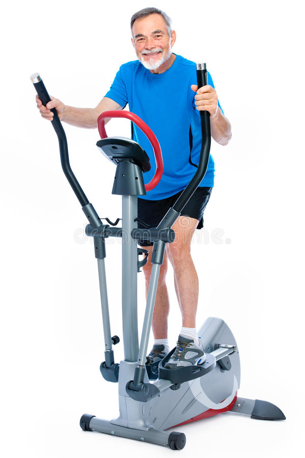 Senior man exercising on stepper. Attractive senior man at health club, exercising on stepper stock photography