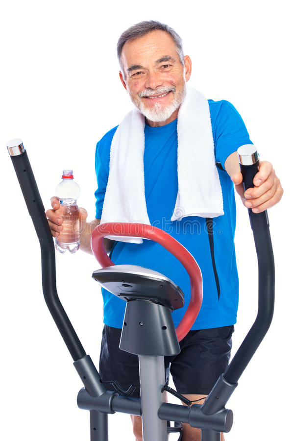 Senior man exercising on stepper. Attractive senior man at health club, exercising on stepper stock images