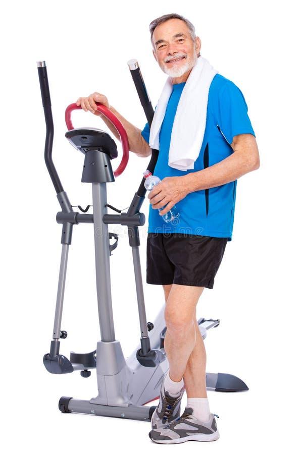 Senior man exercising on stepper. Attractive senior man at health club, exercising on stepper royalty free stock photo