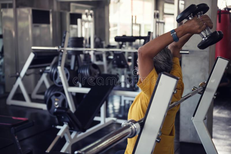 Senior man exerise raising dumbbell in gym. Old senior man exerise raising dumbbell by both hands for arm muscular building with fitness gym equipment background royalty free stock photography
