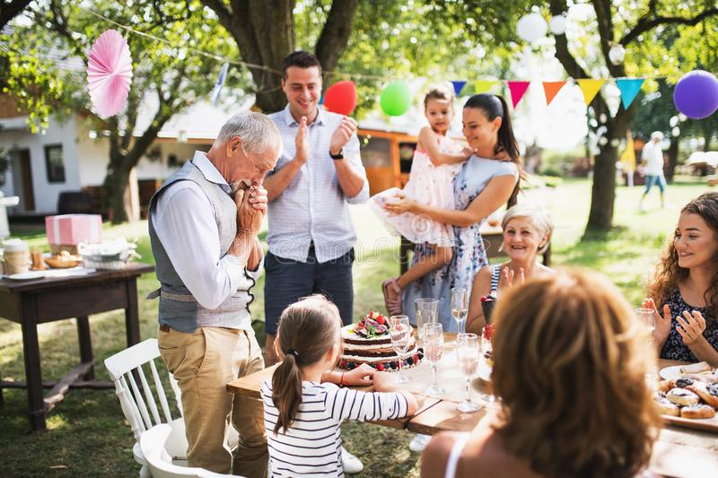 A senior man with an extended family looking at the birthday cake, crying. stock photo
