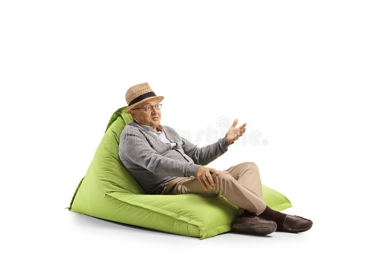 Senior man with face expression resting on a bean-bag armchair and gesturing with hand. Isolated on white background royalty free stock photos