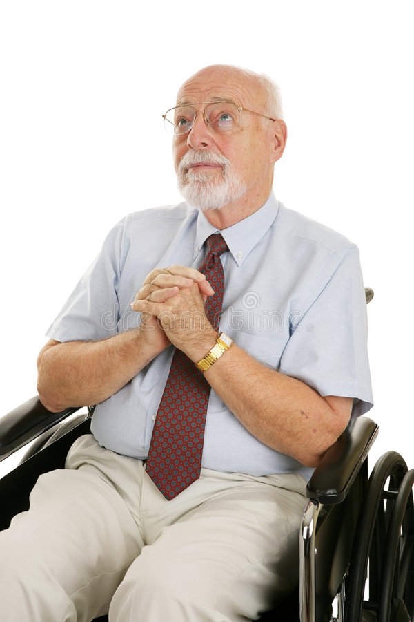 Senior Man of Faith. Senior man in a wheelchair with his hands folded in prayer. Isolated on white royalty free stock images