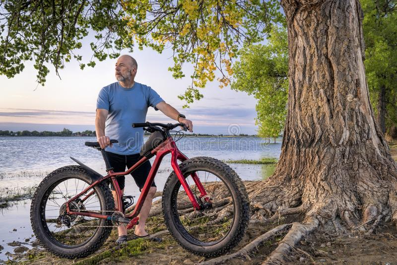 Senior man with a fat mountain bike. Athletic senior man with a fat mountain bike on a lake shore enjoying sunrise - Boyd Lake State Park in northern Colorado stock photography