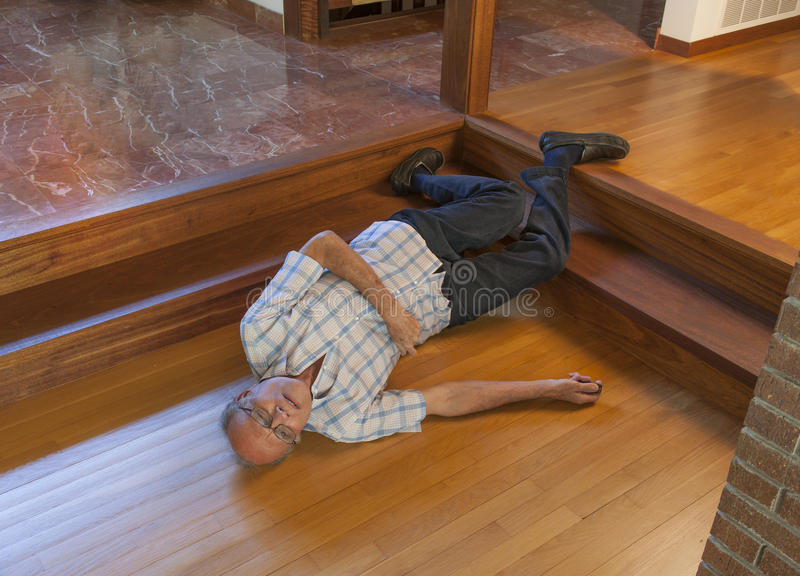 Senior man fell down the stairs. Onto wood floor and is calling for help with the beeper in his right hand royalty free stock image