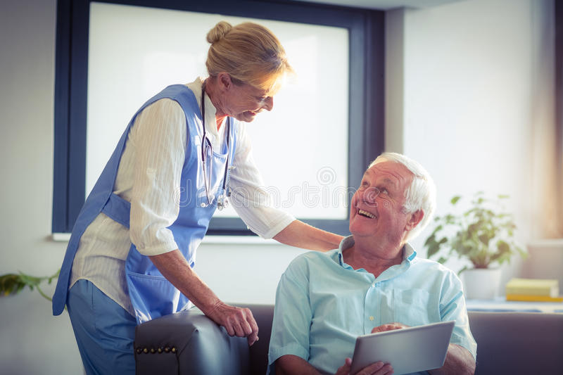Senior man and female doctor interacting with each other stock photos
