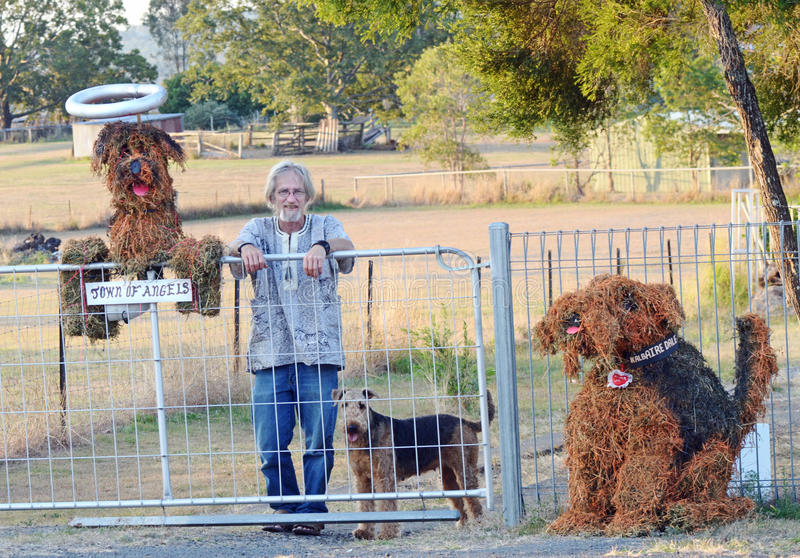 Senior man fence & gate & dog hay sculptures royalty free stock images