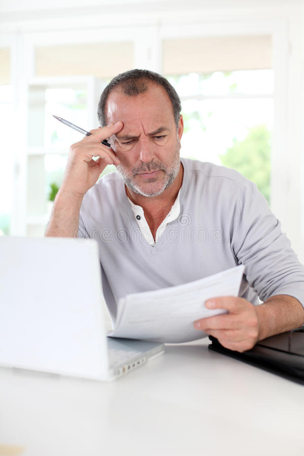Senior man figuring out the tax declaration. Senior man being puzzled with tax documents royalty free stock photos