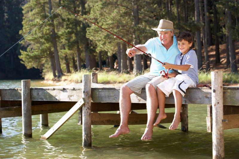 Senior man fishing with grandson stock photography