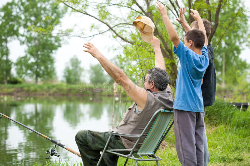Senior man fishing with grandsons. Grandfather and grandsons fishing on weekend stock photos