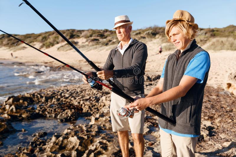 Senior man fishing with his grandson stock photos