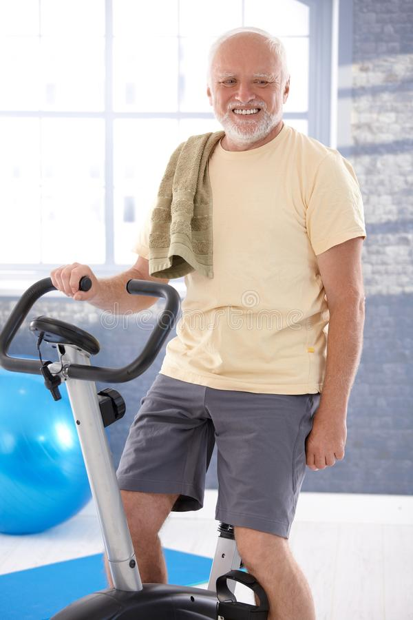 Senior man on fitness cycle smiling stock photography