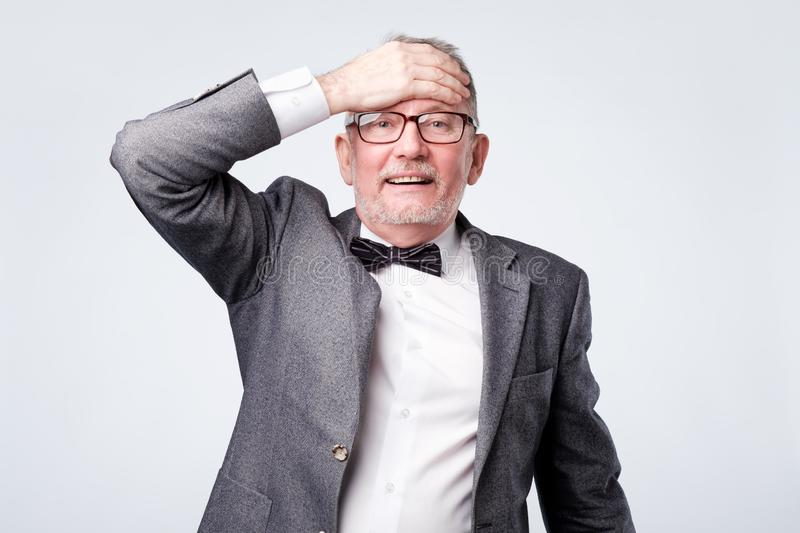 Senior man in formal suit with bow tie surprised with hand on head for mistake royalty free stock photo