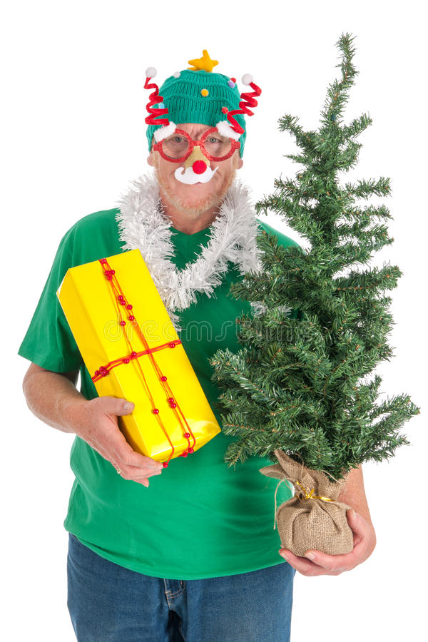 Senior man with funny glasses for Christmas. With present and tree stock photos