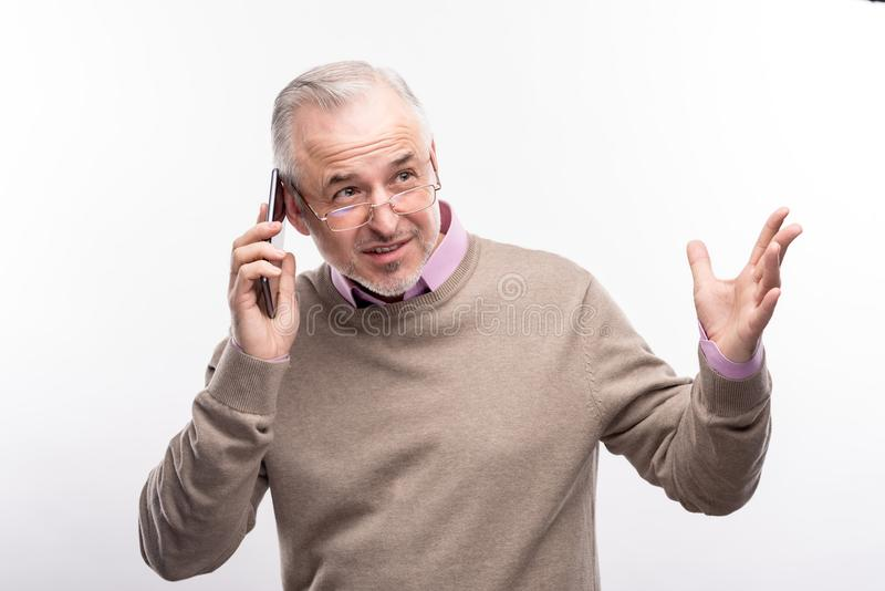 Senior man gesticulating while talking on the phone royalty free stock photo