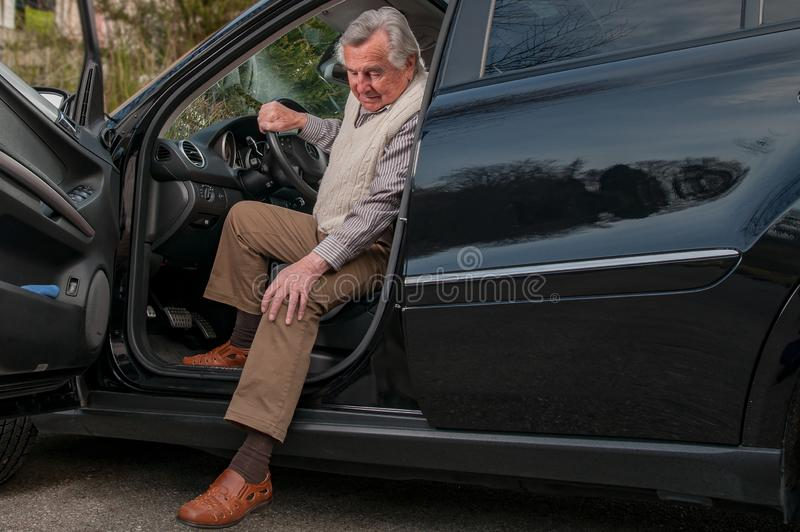Senior man getting out of car. A senior man experiencing some pain while getting out of his car royalty free stock image