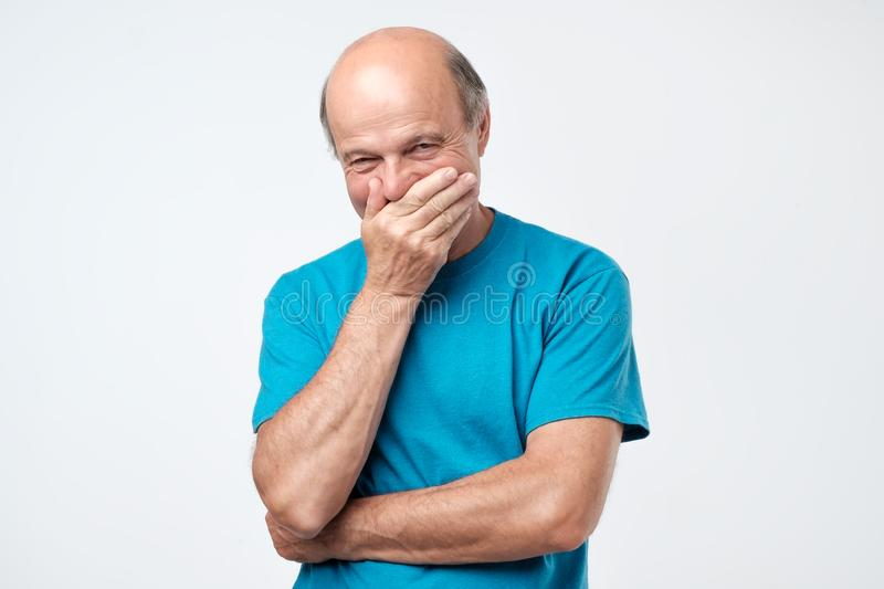 Senior man giggles and covers mouth with his hand. Senior bald hispanic man giggles and covers mouth with his hand royalty free stock images