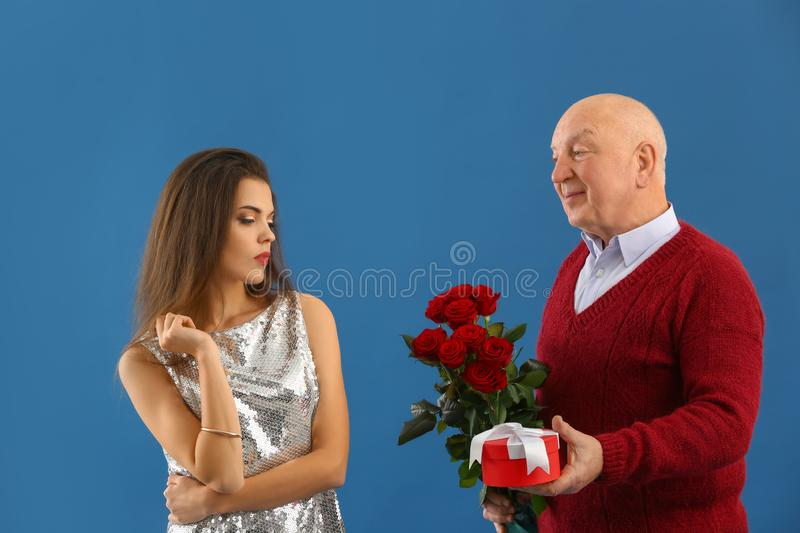 Senior man giving present and flowers to young woman on color background. Marriage of convenience stock photos