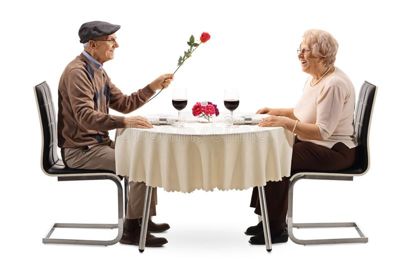 Senior man giving a red rose to a senior woman at a restaurant table. Senior men giving a red rose to a senior women at a restaurant table isolated on white stock images