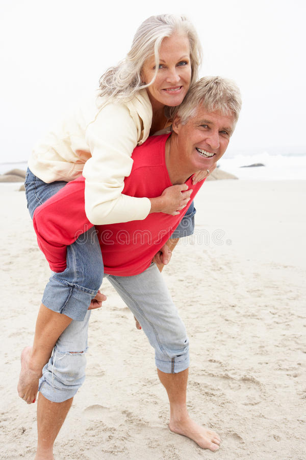 Senior Man Giving Woman Piggyback On Winter Beach stock photography