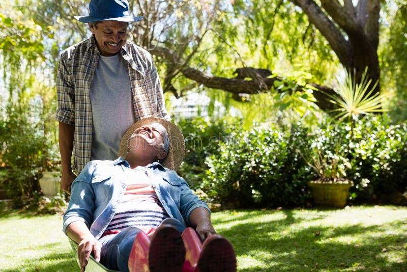 Senior man giving woman ride in wheelbarrow royalty free stock photography