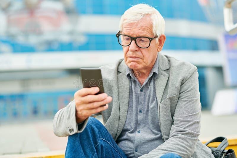 Aged entrepreneur using smartphoneon street stock image