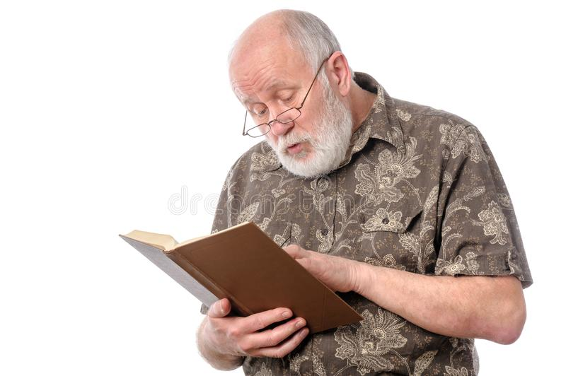 Senior man with glasses reading a book royalty free stock image