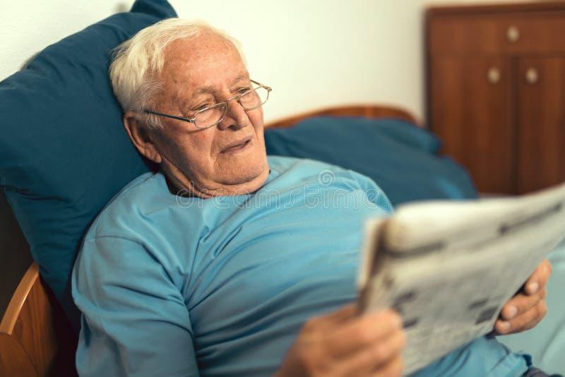 Senior man in glasses reading newspaper royalty free stock photos