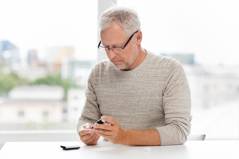 Senior man with glucometer checking blood sugar. Medicine, age, diabetes, health care and old people concept - senior man with glucometer checking blood sugar royalty free stock photography