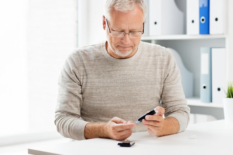 Senior man with glucometer checking blood sugar. Medicine, age, diabetes, health care and old people concept - senior man with glucometer checking blood sugar stock photos