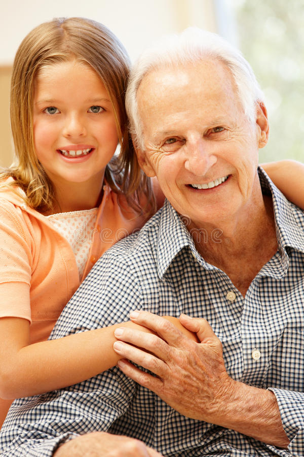 Senior man and granddaughter at home royalty free stock image