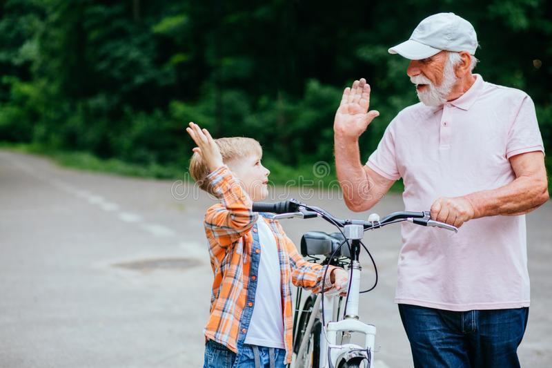 Senior man grandfather and grandson give high five while walking with bicycle in the park royalty free stock image