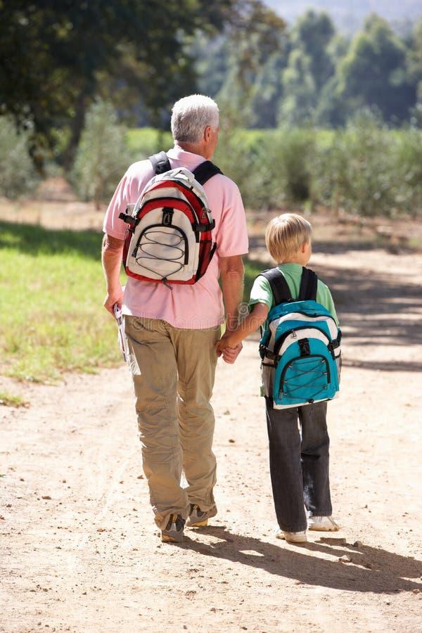Senior man and grandson on country walk royalty free stock photos