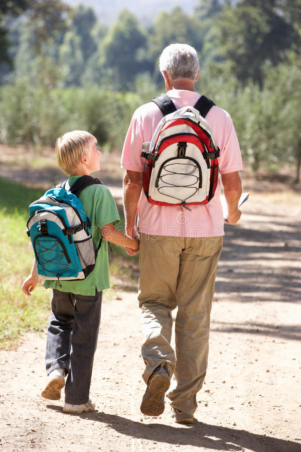 Senior man and grandson on country walk royalty free stock images