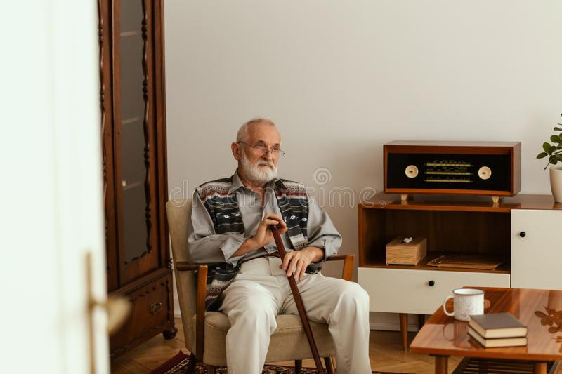 Senior man with grey hair and beard and with walking stick sitting on armchair alone in his apartment royalty free stock images